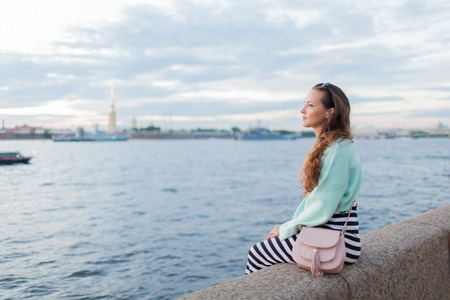 Young and beautiful girl sitting on the embankment of the river. she looks at the sunset and ships passing by. Saint Petersburg, Russia.