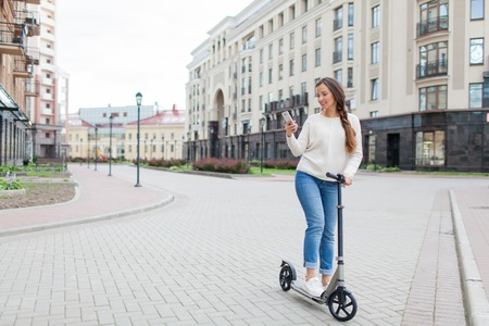 Beautiful, young, and white-toothed girl with long brown hair stopped while riding the scooter, to write to a friend on the phone. She is dressed in a white sweater and blue jeans. Urban background. Stock Photo