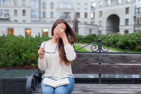 매력적인 여성 손에 안경의 근접 촬영 초상화. 가난한 어린 소녀는 시력 문제가 있습니다. 그녀는 피로 코와 눈을 문지른다. 한 학생이 책을 읽고 공부
