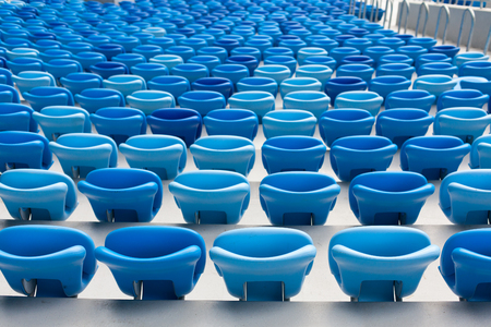 Rows of blue seats at football stadium. Convenient sitting for all.