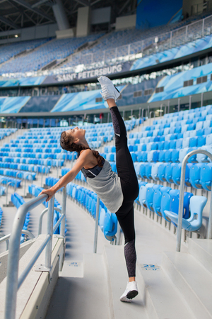 Young sporty girl doing workout at the stadium. She raised her leg up over head. Woman in sportswear a great stretch. Stock Photo