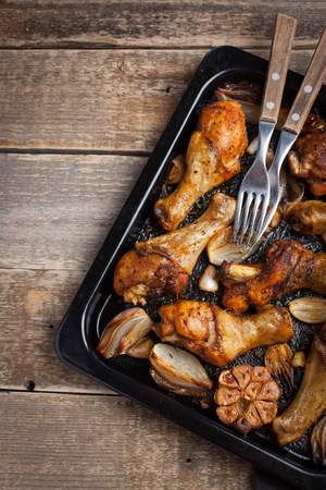 Oven baked chicken legs with onions, garlic and peppers on a dark wooden background closeup. Top view with copy space. Wooden rustic table.