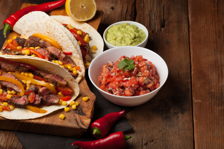 Three Mexican tacos with marbled beef, black Angus and vegetables on old rustic table. Mexican dish with sauces guacamole and salsa in bowls. Stock Photo