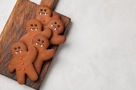 Homemade ginger biscuits in the shape of gingerbread men for Halloween. On the lighter concrete background. Top view with copy space.