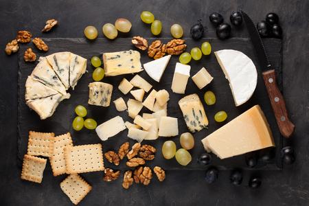 Geassorteerde kazen met witte druiven, walnoten, crackers en witte wijn op een stenen bord. Eten voor een romantische date op een donkere achtergrond. Bovenaanzicht.
