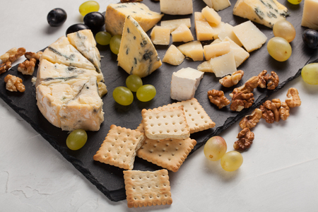 tabla de quesos: Assorted cheeses with white grapes, walnuts, crackers and on a stone Board. Food for a romantic date on a light background. Foto de archivo