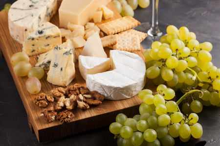 tabla de quesos: Assorted cheeses with white grapes, walnuts, crackers and white wine on a wooden Board. Food for a romantic date on a dark stone background. Top view.