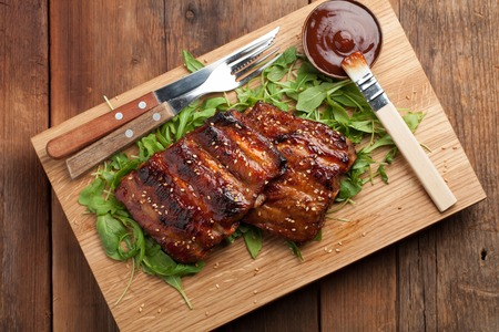 Closeup of pork ribs grilled with BBQ sauce and caramelized in honey on a bed of arugula. Tasty snack to beer on a wooden Board for submission on the old wooden background. Top view. Stock Photo