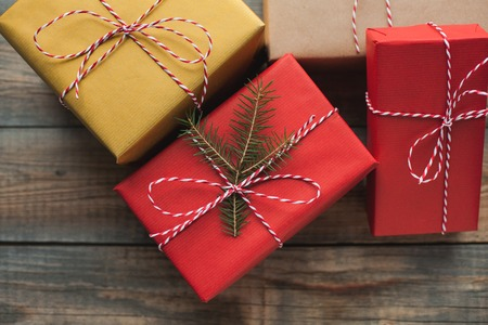 Christmas background with gift boxes on wooden background. Top view. Beautifully packaged multi-colored gifts for the new year or the day of the holy valentine. Stock Photo
