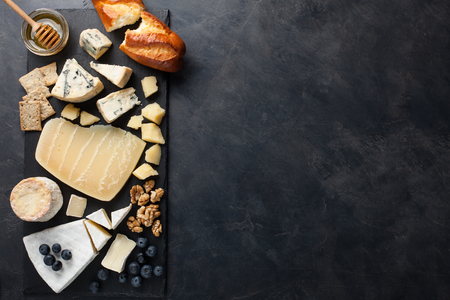 Tasting cheese dish on a dark stone plate. Food for wine and romantic date, cheese delicatessen on a black concrete background. Top view with copy space.
