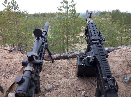 Assault rifle and machine gun on the background of pine forests and sand