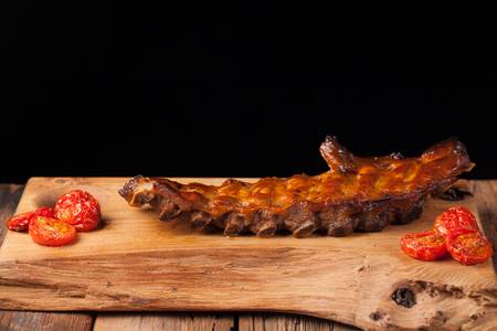Pork ribs in barbecue sauce and honey roasted tomatoes on a wooden Board. A great snack to beer on a black background. With copy space.