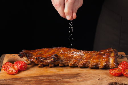 The chef sprinkles salt in ready to eat pork ribs, lying on an old wooden table. A man prepares a snack to beer on a black background with copy space.