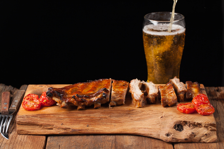 Pork ribs in barbecue sauce and honey baked tomatoes on the old wooden table. Meats and light beer on black background with copy space. In the background poured the beer into the glass.