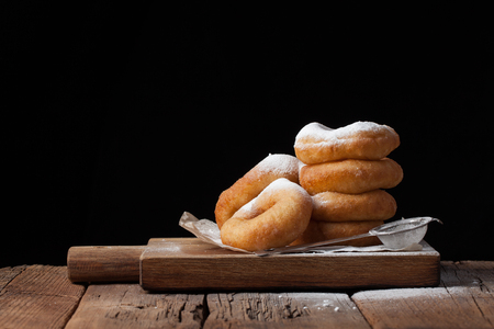 Sweet donuts with powdered sugar on a black background. Tasty, but harmful food on an old wooden table with copy space