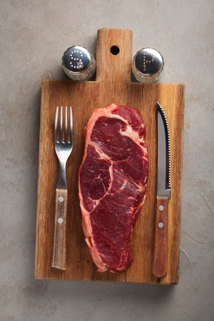 Raw beef marbled steak with vintage white Cutlery on old stone background. A piece of meat on a wooden Board. Steak New York. Top view with copy space Stock Photo