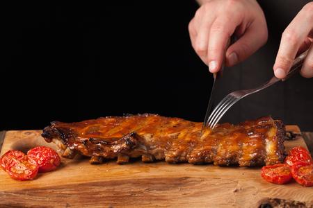 シェフは古い木製のテーブルの上に横たわる鋭いナイフで豚カルビを食べる準備ができてそれをカットします。男は、コピー領域と黒い背景にビー 写真素材