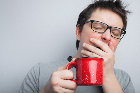 Sleepy yawning man in eyeglasses with red cup of tea or coffee has uncombed hair in underwear on light background, morning refreshment and drink. Copy space for your text.