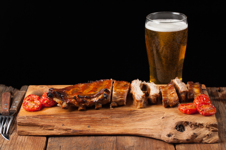 Pork ribs in barbecue sauce and honey baked tomatoes on the old wooden table. Meats and light beer on black background with copy space