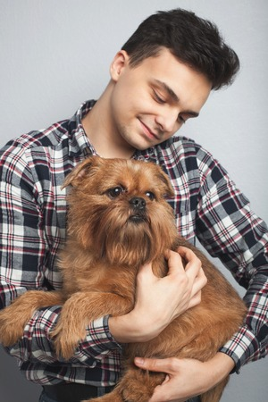 Closeup portrait handsome young hipster man, kissing his good friend red dog isolated light background. Positive human emotions, facial expression, feelings.