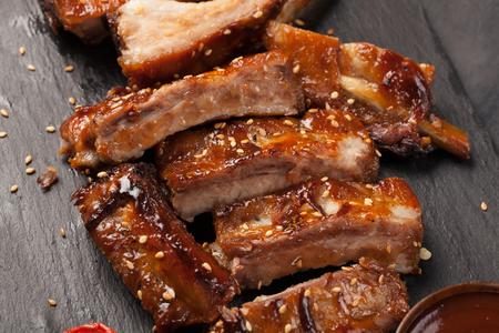 côtes de porc dans la sauce barbecue et les tomates rôties sur un tableau noir à l & # 39 ; ardoise . un peu de collation pour une collation noire sur fond de pierre. vue de dessus en bois Banque d'images