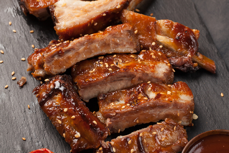 Pork ribs in barbecue sauce and honey roasted tomatoes on a black slate dish. A great snack to beer on a black stone background. Top view.