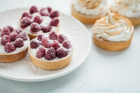 Delicious lemon and raspberry tartlets with meringue on a white vintage plate. Sweet treat on a light blue background.