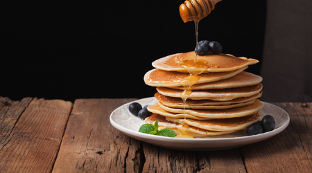 The chef pours honey pancake stack with blueberries and mint on black background. Copy space for your text.