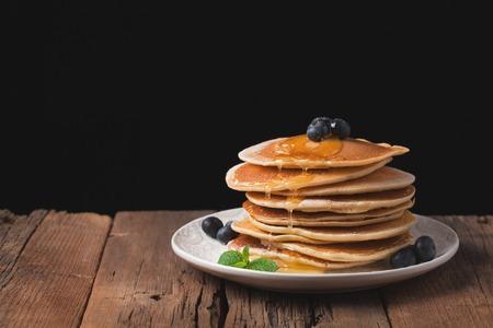 木製の素朴なテーブルの上にブルーベリーと蜂蜜のパンケーキ。黒い背景に朝食のためのデザート。テキストのスペースをコピーします。 写真素材