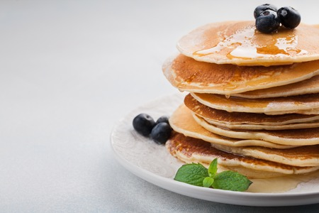 A stack of delicious pancakes with honey and blueberries on a light blue background. with copy space. Foto de archivo