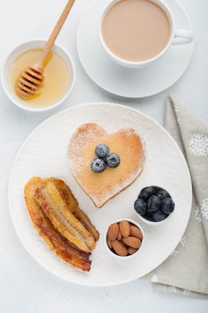 A stack of delicious pancakes with honey, coffee and blueberries on a light blue background. Great Breakfast for Valentines day. Top view. Stock Photo
