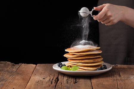 Pila de crepes con azúcar en polvo de especias para cocinar en la mano del cocinero en el fondo de madera oscura . espacio para el espacio de texto . Foto de archivo - 95128587