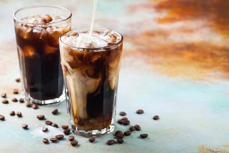 Ice coffee in a tall glass with cream poured over and coffee beans. Cold summer drink on a blue rusty background with copy space.