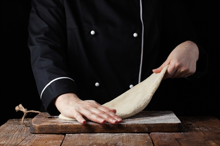 Chef kneading dough, Making dough by female hands at bakery on a black background.