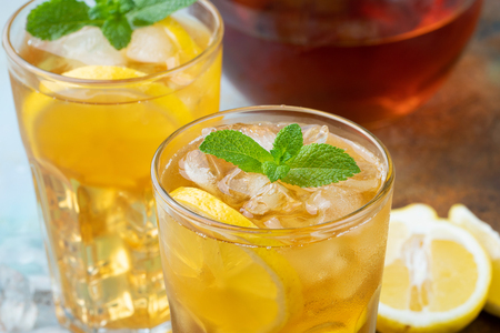 Traditional iced tea with lemon, mint and ice in tall glasses. Two glasses with cool summer drink on old rusty background.
