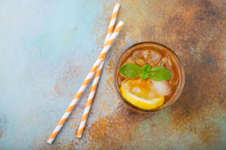 Traditional iced tea with lemon, mint and ice in tall glasses. A glass of refreshing summer drink on the old rusty background. Top view with copy space.