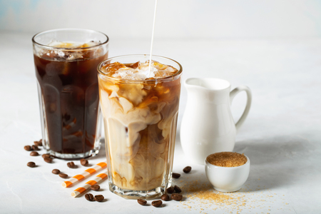 Ice coffee in a tall glass with cream poured over and coffee beans. Cold summer drink on a light blue background. Standard-Bild