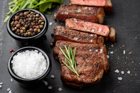 Closeup ready to eat steak new York beef breeds of black Angus with herbs, garlic and butter on a stone Board. The finished dish for dinner on a dark stone background. Top view. Stock Photo
