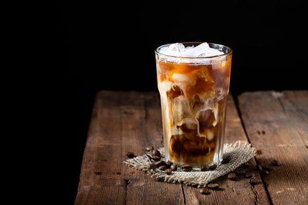 Ice coffee in a tall glass with cream poured over and coffee beans on a old rustic wooden table. Cold summer drink on a dark wooden background with copy space. Standard-Bild