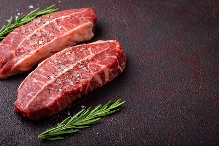 Raw fresh meat Top Blade steaks on dark background. top view with copy space
