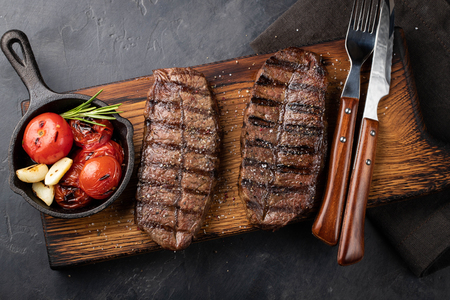 Closeup ready to eat steak Top Blade beef breeds of black Angus with grill tomato, garlic and on a wooden Board. The finished dish for dinner on a dark stone background. Top view