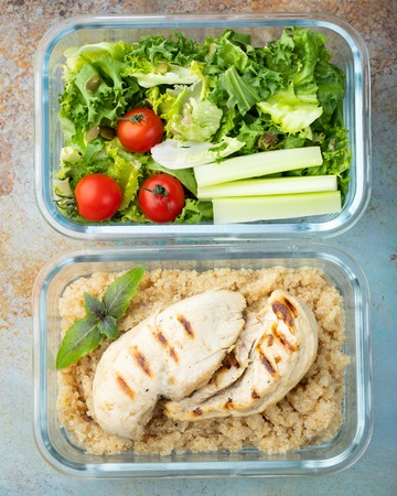 Healthy meal prep containers with quinoa, chicken breast and green salad overhead shot. Top view. Flat lay. 免版税图像