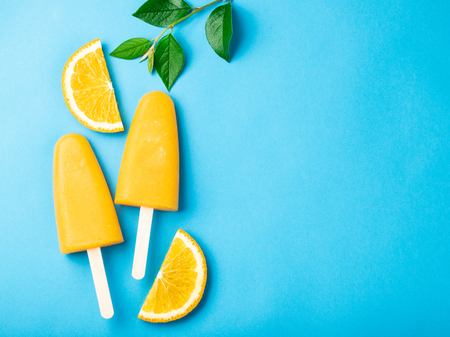 Orange ice cream with juice on a blue bacground. Ice pops, flat lay, top view with copy space.