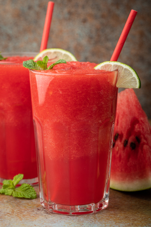 Watermelon slushie with lime, summer refreshing drink in tall glasses on a blue rusty background.