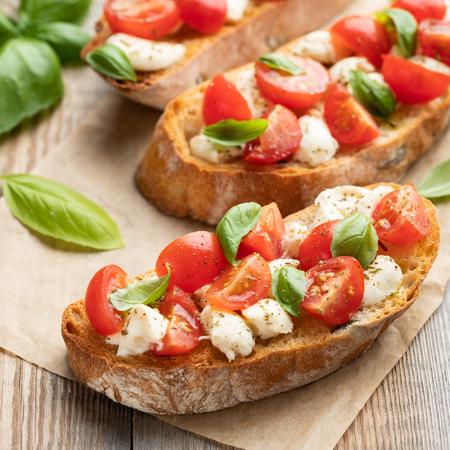 Bruschetta aux tomates, fromage mozzarella et basilic sur une vieille table rustique. Apéritif ou collation italienne traditionnelle, antipasti.