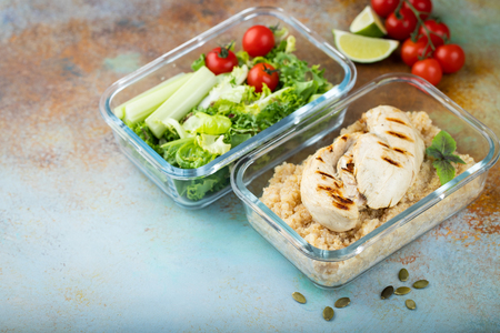 Healthy meal prep containers with quinoa, chicken and green salad overhead shot with copy space.
