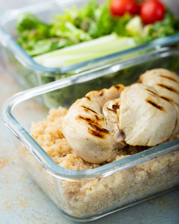 Healthy meal prep containers with quinoa, chicken breast and green salad overhead shot.