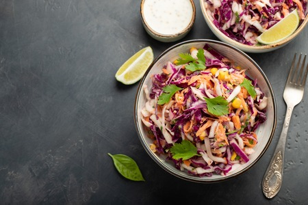 Purple cabbage and carrot salad with mayonnaise in a white bowl on a black background. Classic coleslaw. Diet vegetarian dish. Top view with copy space Фото со стока