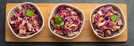 Purple cabbage and carrot salad with mayonnaise in a white bowl on a black background. Set of three classic coleslaw salad. Diet vegetarian dish. Top view.