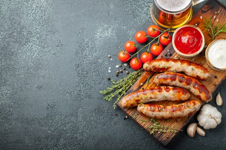 Fried sausages with sauces and herbs on a wooden serving board. Great beer snack on a dark background. Top view with copy space. Stockfoto